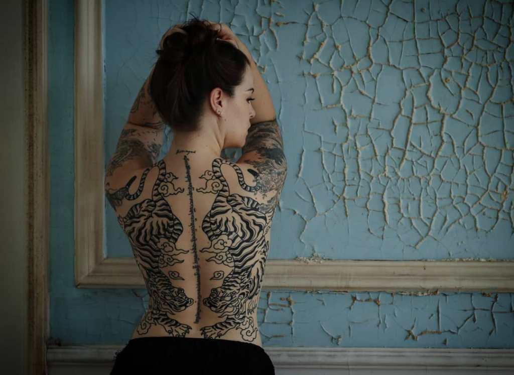 Татуировка на спине у девушки надпись